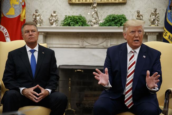 川普總統20日在白宮會見到訪的羅馬尼亞總統Klaus Iohannis(左)時,對媒體表示考慮多種暫時減稅方案提振經濟發展。(Getty Images)