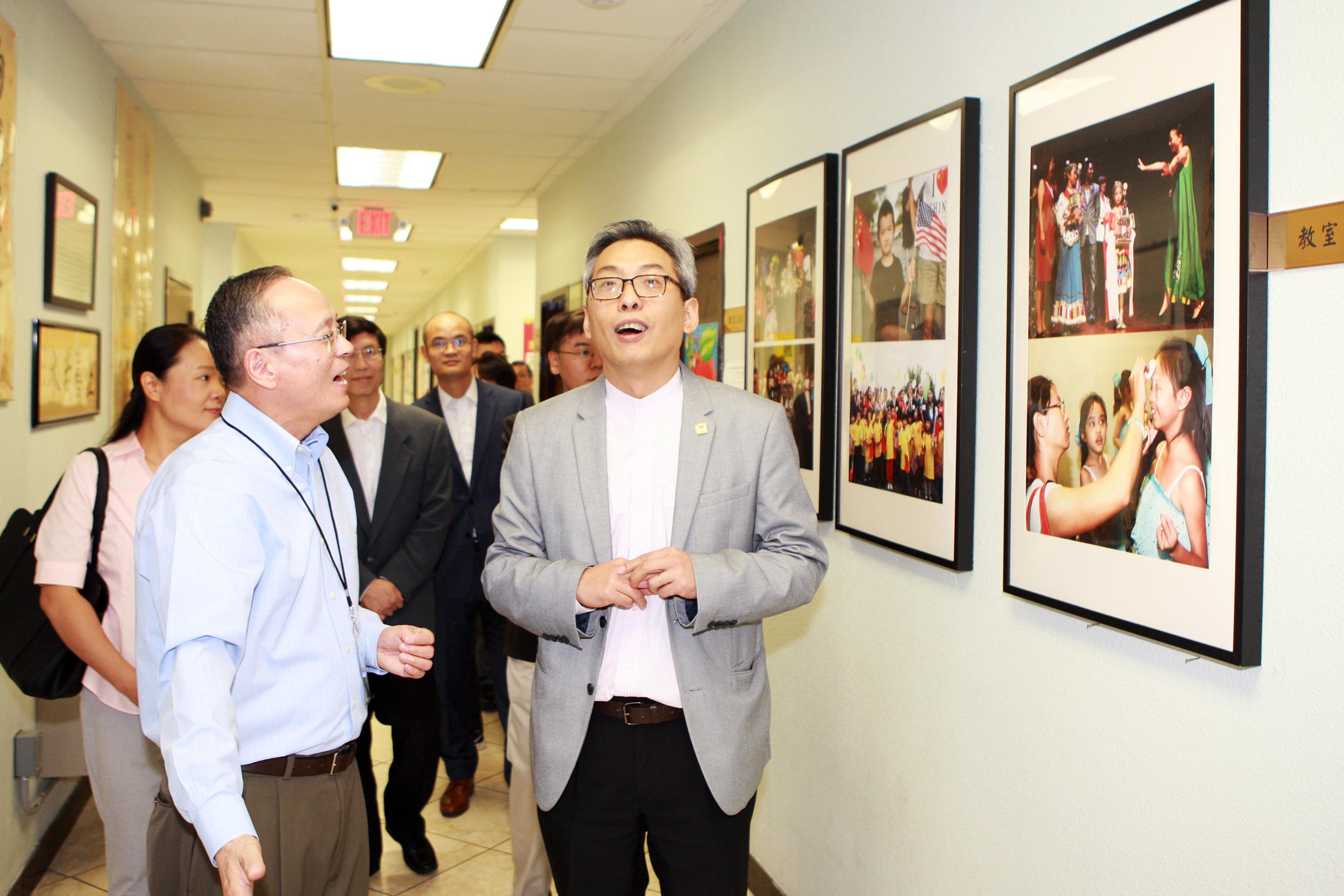 華夏中文學校總校長包華富(左二)、理事長朱莉(左一)陪同蔡偉(右一)參觀校舍。(記者賈忠/攝影)