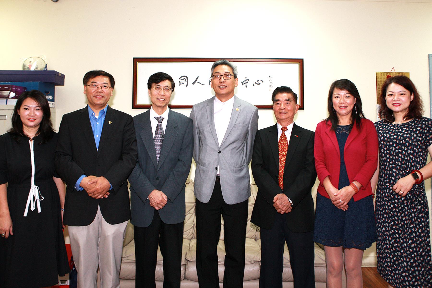 蔡偉(中)與中國人活動中心部分理事在中心辦公室合影。(記者賈忠/攝影)