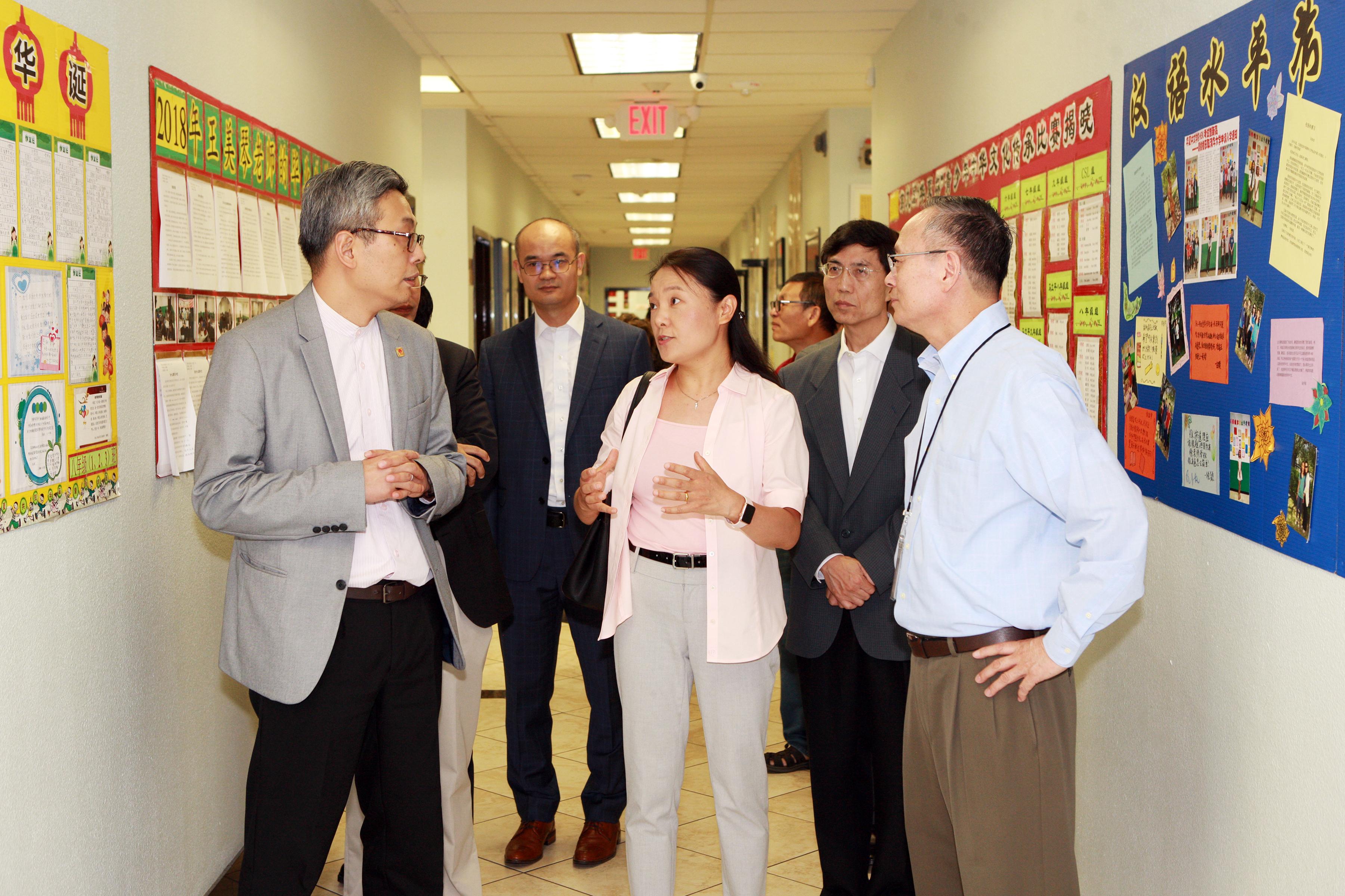 華夏中文學校總校長理事長朱莉(中)向蔡偉(左一)介紹學校情況。(記者賈忠/攝影)