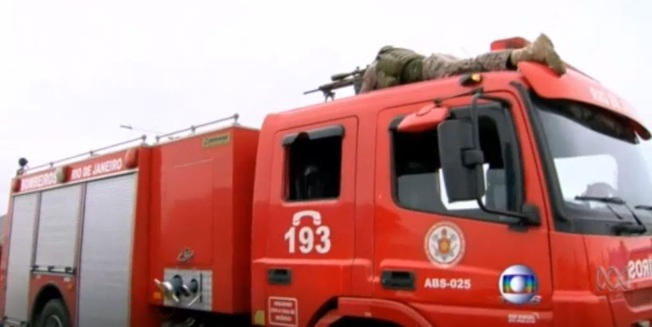 狙擊手趴在消防車車頂,等候開槍時機。(取材自澳洲新聞網影片)