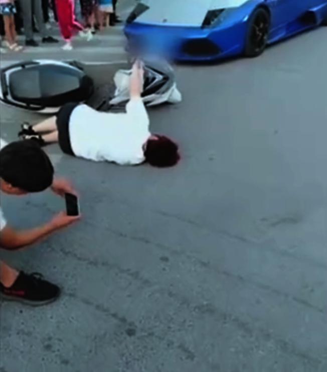 網紅不僅占用十字路口斑馬線拍視頻,還躺在地上打滾。(視頻截圖)
