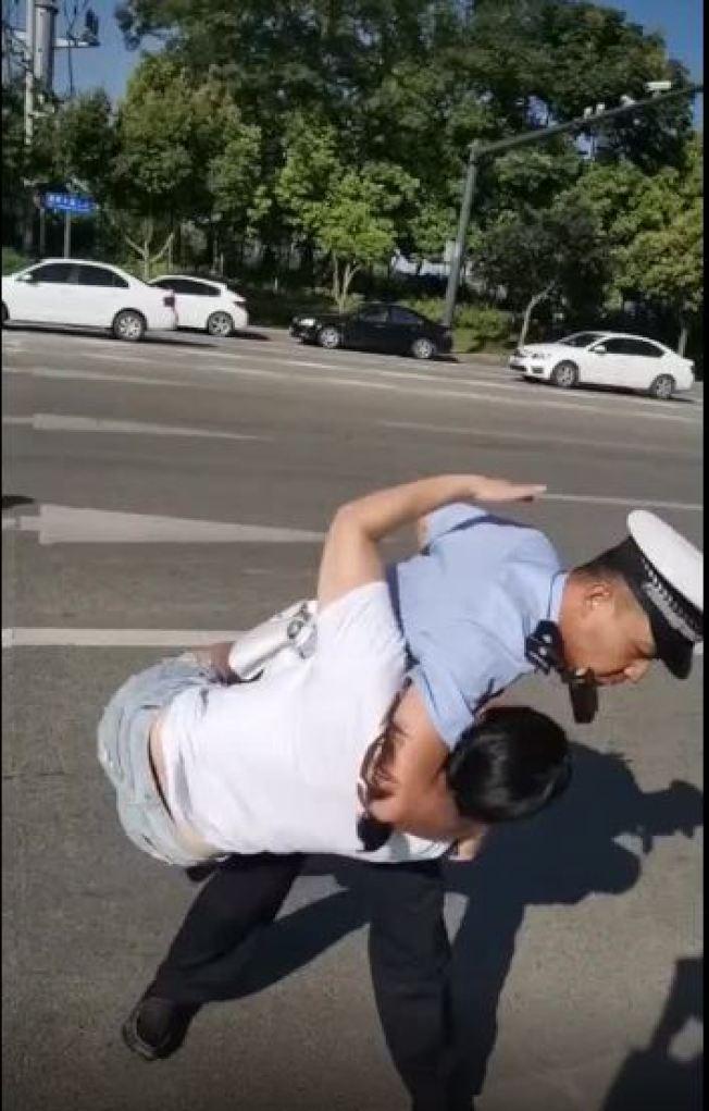 女子未繫安全帶被查後拒罰,街邊撒潑,被交警抱摔按倒。(視頻截圖)