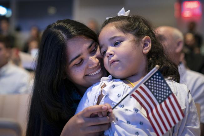 川普總統21日再提廢除出生公民權之議,以阻止外國婦女專程前來美國生孩子。圖為一名母親和女兒參加入籍儀式。(Getty Images)
