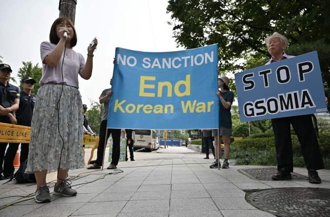 南韓首爾有反戰社運人士21日趁美國對北韓政策特別代表畢根到訪時抗議,舉起終止韓戰、停止制裁,和停止「韓日軍事情報保護協定」的標語牌。(Getty Images)