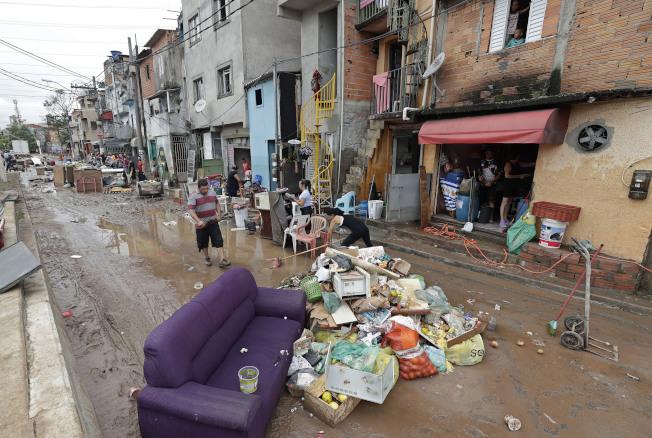 巴西森林濫伐嚴重,水土保持落後,每逢雨季,洪水氾濫,聖保羅街道積水,一片泥濘。(美聯社)