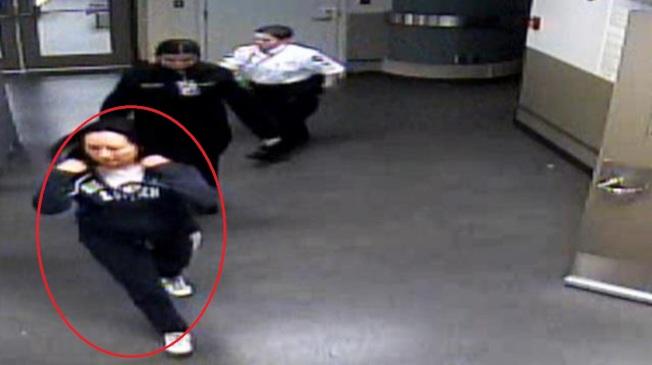 孟晚舟去年在溫哥華機場被捕時,身穿一件藍色的連衣帽(畫紅圈者)。影片截圖