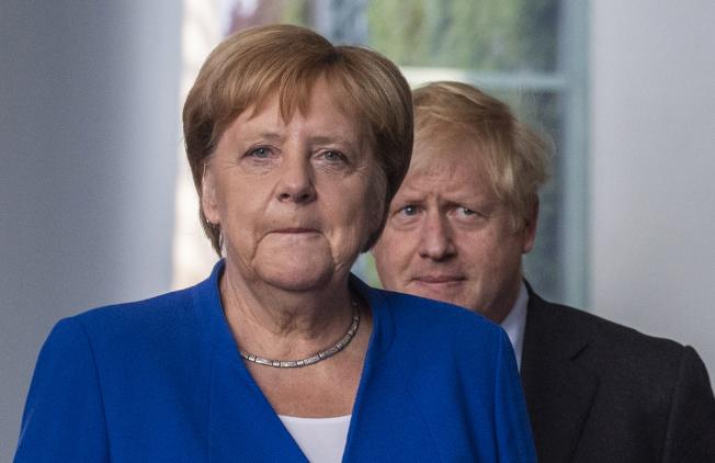 德國總理梅克爾(左)21日在首都柏林歡迎來訪的英國首相強生。(Getty Images)