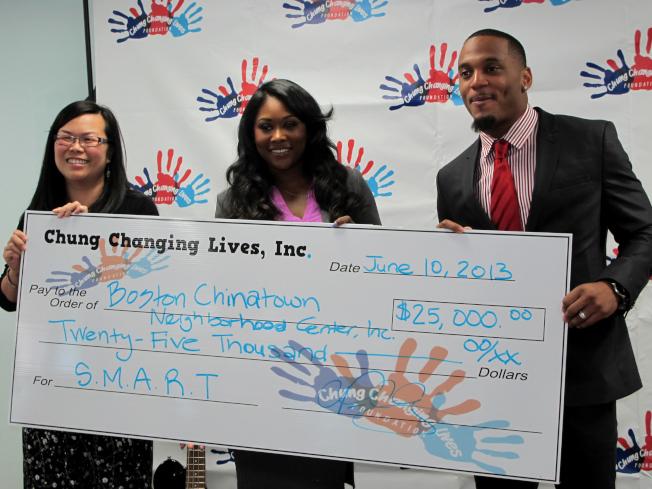 鍾家庭(右)因非法持有毒品被起訴,圖為2013年他與妻子一同捐款2.5元給波士頓華埠社區中心。(本報檔案資料)