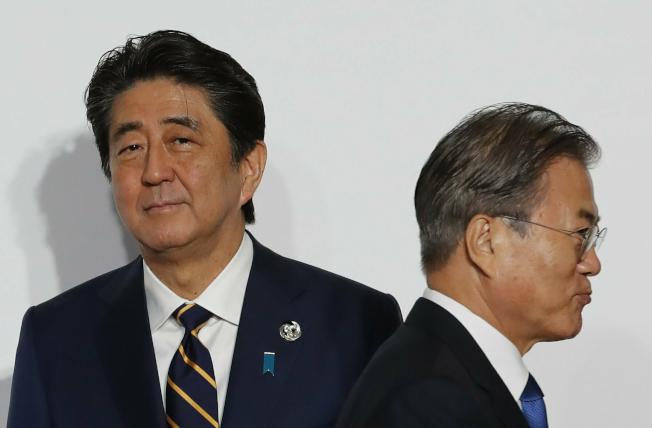 南韓21日宣布,終止與日本簽署的軍事情報保護協定。雙方關係跌入冰谷。圖為今年6月底,日本首相安倍(左)與韓國總統文在寅(右),兩人在大阪G20峰會上擦身而過,沒有交集。(美聯社)