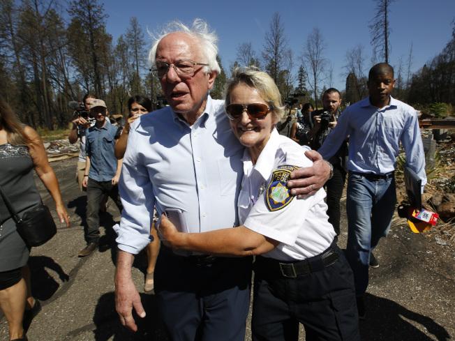 民主黨總統參選人桑德斯(前左)22日公布耗資16兆3000億元的對抗氣候變遷計畫,2050年達成改用再生能源的目標。圖為他走訪加州天堂鎮,和一名當地義警擁抱。(美聯社)