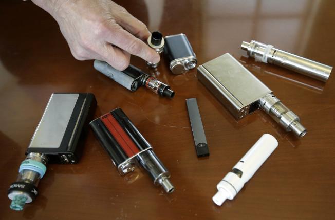 最近出現的神秘肺部疾病,疑與越來越多人吸用的電子菸有關,引起公衛單位注意,展開調查。圖為一位麻州的高中校長展示在校搜到的各種違禁電子菸。(美聯社)