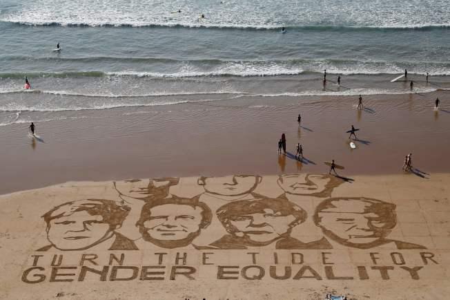 G7峰會24日至26日在法國西南部城市比亞里茲(Biarritz)舉行,圖為藝術家在海灘上繪出七 國元首的肖像沙畫。(Getty Images)