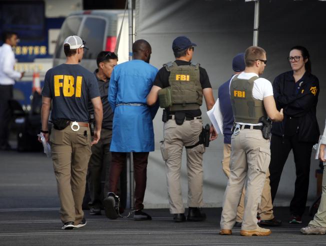 一名嫌犯在洛杉磯城中區一個停車場被捕,手銬腳鐐上身。(美聯社)
