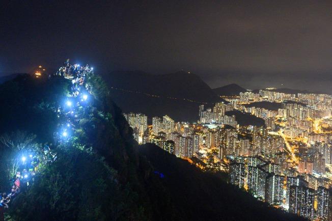 港人23日自發登上獅子山,以手機燈光照亮山脊線。(Getty Images)