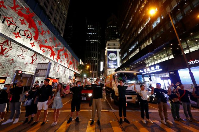 「香港之路」串起多個地鐵線路,並在港島、九龍和新界三大地區手牽手築成人鏈,要求港府回應五項訴求。圖為港島中環附近的人鏈。(路透)