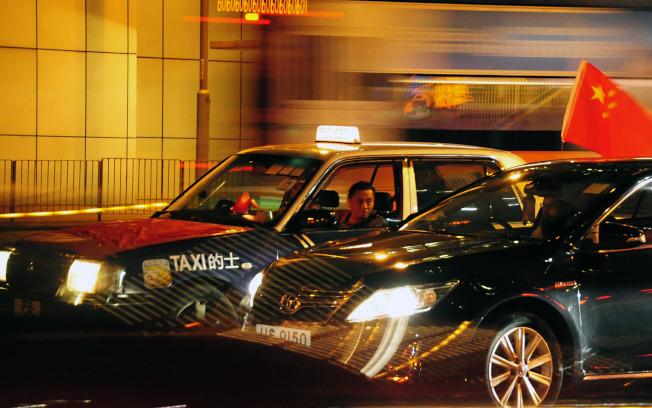 香港23日晚「香港之路」活動期間,有數十輛掛著五星旗的計程車從人鏈旁呼嘯而過。(中央社)