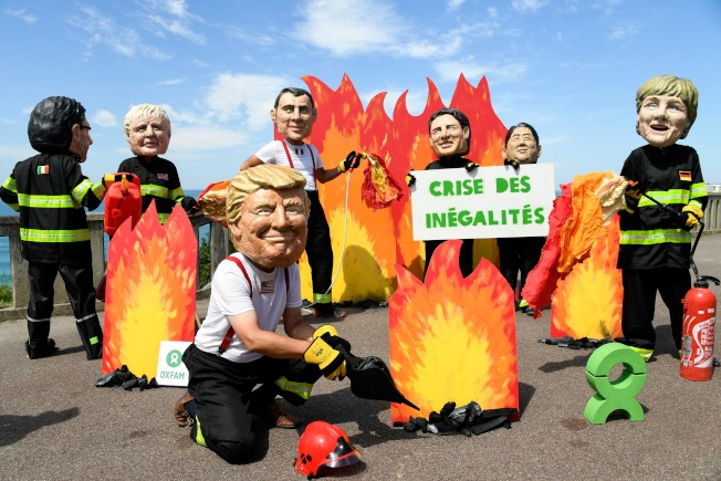 G7峰會24日起在法國舉行,法國總統馬克宏呼籲會中討論亞馬遜雨林火災。「樂施會」成員打扮成川普總統及多國元首模樣,有的點火,有的滅火。(Getty Images)