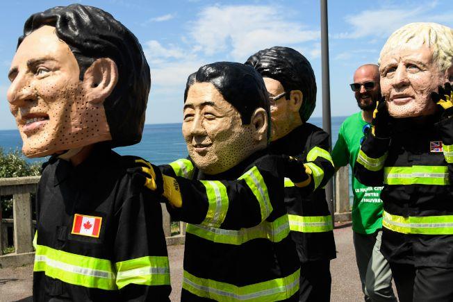 G7峰會24起在法國舉行,「樂施會」成員穿著消防隊員的衣服,扮演加拿大總理杜魯多 (左)、日本首相安培(中)、英國首相強生(右)的模樣。(Getty Images)