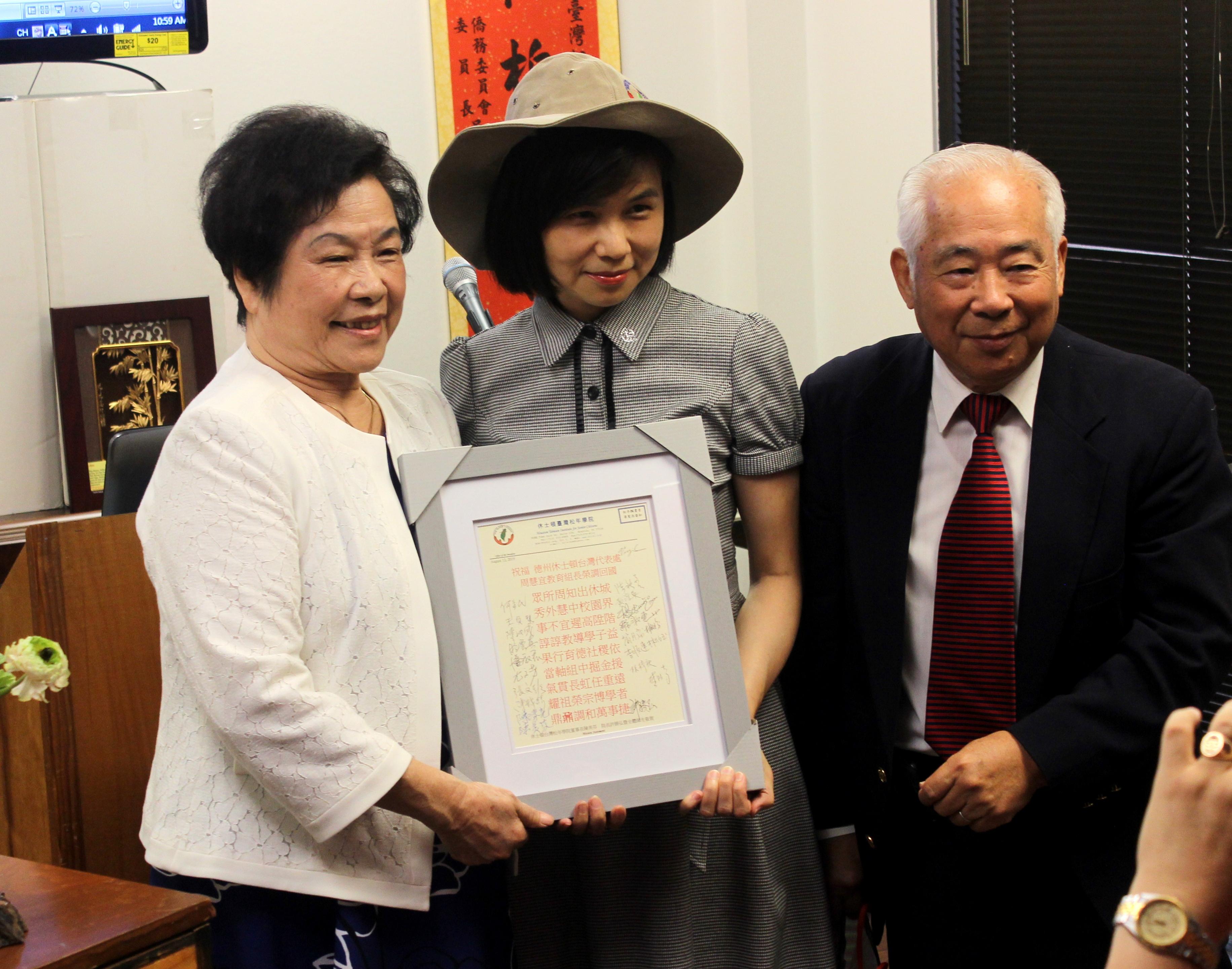 許勝弘(右)和陳美芬(左)贈感謝狀予周慧宜,並以「藏頭詩」表達祝賀。(記者盧淑君/攝影)