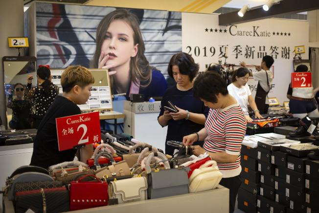 美中貿易戰再度升溫並惡化,互相加徵從對方進口產品關稅。圖為北京商場內購物者正在選購手袋。(美聯社)