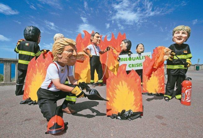 G7峰會在法國比亞里茨舉行,適逢亞馬遜雨林連日大火,維權人士戴上各國領袖的面具上演行動劇,呼籲拿出具體行動。 美聯社