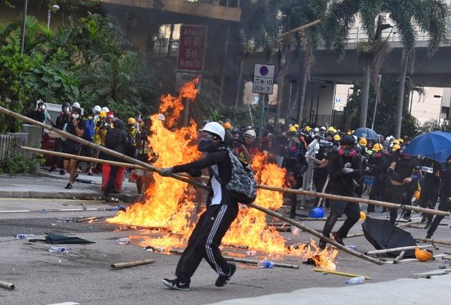 8月24日下午約4時許,警方於觀塘偉業街一帶驅散堵路示威者,期間有示威者向警方投擲燃燒彈及磚頭等雜物,警方多次警告後施放催淚彈驅散。  香港中通社圖片