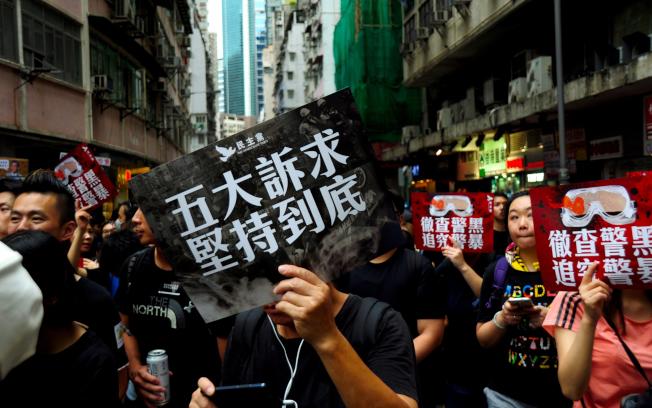 反送中激化中港矛盾,「港漂」記者Kris表示,多數港漂對香港社會保持距離、戒心,在官方的愛國主義宣傳下,很容易將爭取自由民主的運動都視為「港獨」。圖為18日維多利亞公園集會時,民眾高舉訴求標語。(中央社資料照片)