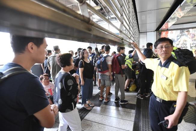 因應24日下午的觀塘遊行,港鐵中午12時起暫停觀塘線彩虹站至調景嶺站之間列車服務。圖為觀塘站工作人員將車站關閉。(中通社)