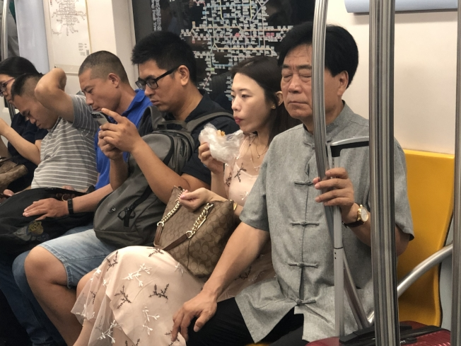 北京地鐵下「禁食令」後,仍有乘客於早晨上班尖峰時段大吃早點。(記者許依晨/攝影)