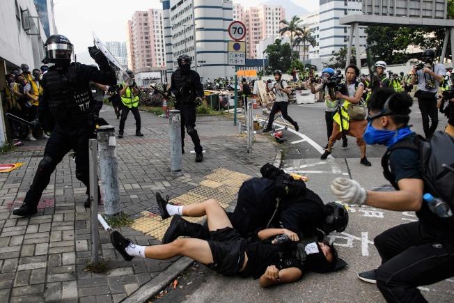 香港反送中示威者24日在多為工人社區的九龍灣,與警方發生嚴重衝突,被打壓在地。(Getty Images)