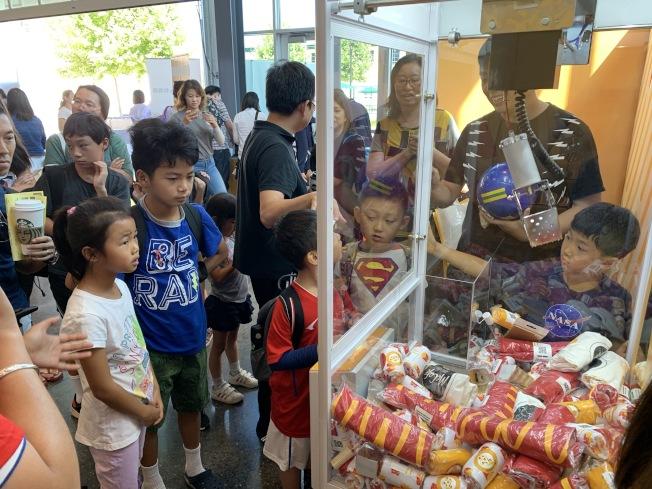娃娃機中放著麥當勞Tshirt、襪子等獎品,是活動亮點,吸引大小朋友圍觀。(記者林亞歆/攝影)