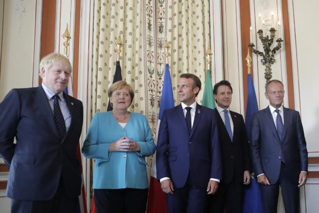 法國總統馬克宏(中)24日歡迎出席G7峰會的各國領袖,左起第一次與會的英國新首相強生、德國總統梅克爾、義大利總理康提及歐洲理事會主席圖斯克。(美聯社)