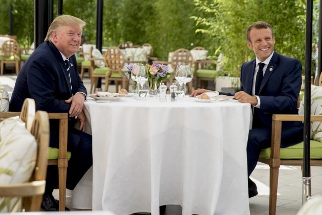 美國總統川普(左)與今年G7峰會東道主法國總統馬克宏(右)24日共進午餐,川普表示與馬克宏處得不錯。(美聯社)