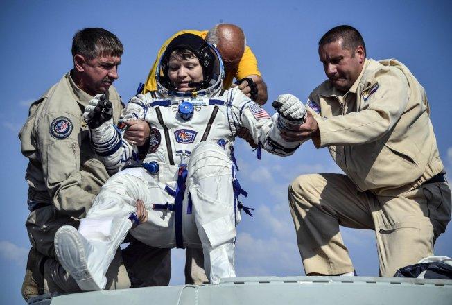 美籍太空人麥克林(圖中)因首起太空犯罪指控而接受調查。圖為她在2019年6月25日自太空返回地球後,由地面人員協助離開太空艙的檔案照。路透