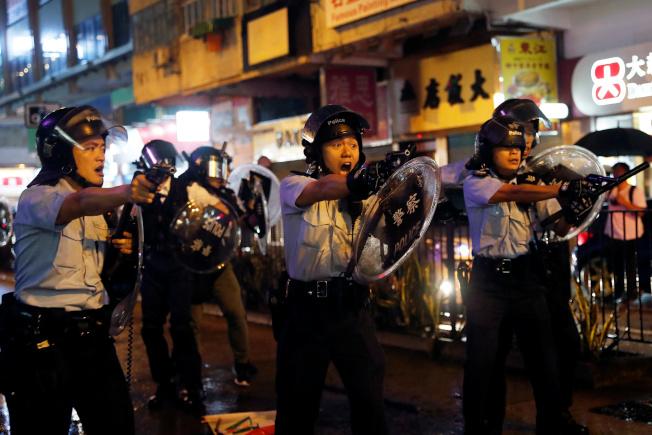 香港昨舉行荃葵青遊行,再爆激烈警民衝突。其間,三名警察拿起手槍瞄準示威者,並對空鳴槍,為反送中抗爭以來的首次。(路透)