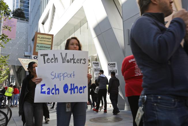 臉書的技術雇員7月16日在舊金山遊行支持該公司的餐廳員工,後者因新合約問題聚集抗議。(美聯社)