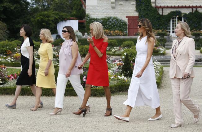 G7夫人逛花園,左起為日本首相夫人安倍昭惠、歐洲理事會主席圖斯克之妻瑪寇札塔‧圖斯克、澳洲總理夫人珍妮·莫里森、碧姬‧馬克宏、梅蘭妮亞,以及智利第一夫人塞西莉亞·莫雷爾。(美聯社)