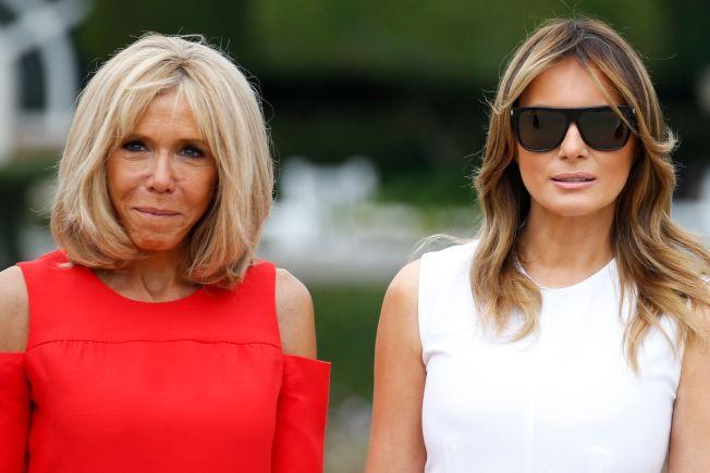 法國第一夫人碧姬‧馬克宏(左)25日一身鮮紅洋裝,小露香肩,帶領美國第一夫人梅蘭妮亞等人逛花園。(Getty Images)