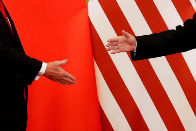 美中兩隻大象打架,讓很多國家與產業受影響,如何平息,國際關切。圖為2017年11月川普總統(左)在北京與習近平主席(右)握手。(路透)