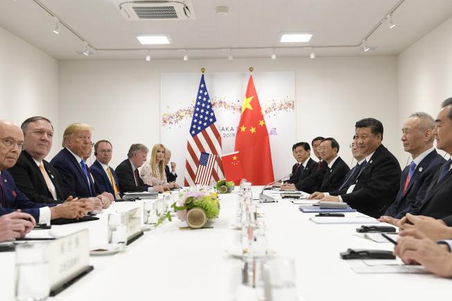 川普總統宣稱可動用緊急國安法規要求美國廠商撤離中國,但可能只是紙老虎的說法。圖為今年6月底在日本大阪G20峰會上的美中雙邊經貿會談。(美聯社)