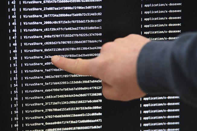 駭客今年夏天入侵長島兩個學區的電腦系統,鎖住其中資料,迫使其中一個學區支付價值8萬8000元的加密貨幣。圖為專家在巨大屏幕顯示遭勒索軟體感染的電腦。(Getty Images)