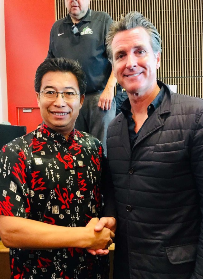 東洛杉磯學院現代語言系終身教授劉榮文(左),讚許州長紐森(右)的兩年社區學院的免學費計畫。(劉榮文提供)