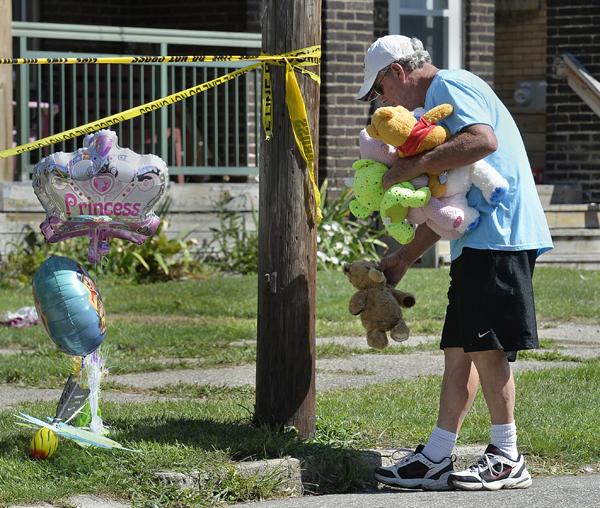 賓州伊利鎮「哈里斯家庭托兒所」11日凌晨發生大火,奪去五名兒童的性命。一名男子在火災現場門外擺放氣球和絨毛玩偶作悼念。(美聯社)