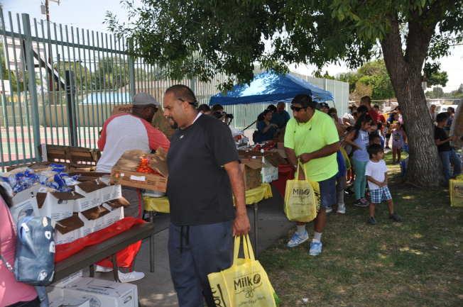 低收入民眾領取免費的新鮮蔬菜和水果。(記者張越/攝影)