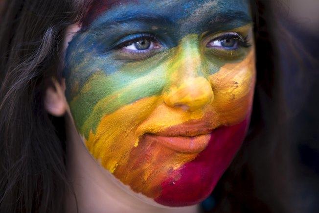 一名少女在臉上塗上彩紅顏色,參加以色列同志大遊行。(路透)