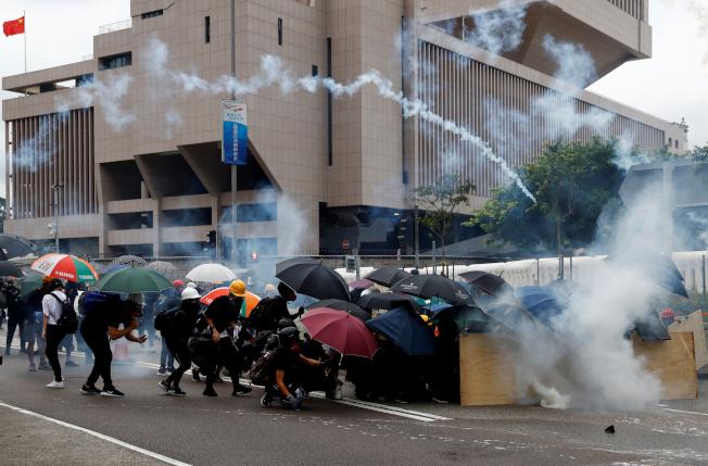 香港反送中示威者無視警方禁止遊行令命,831大示威引爆與警方衝突 ,警方發射催淚彈,示威人群紛紛躲避。(路透)