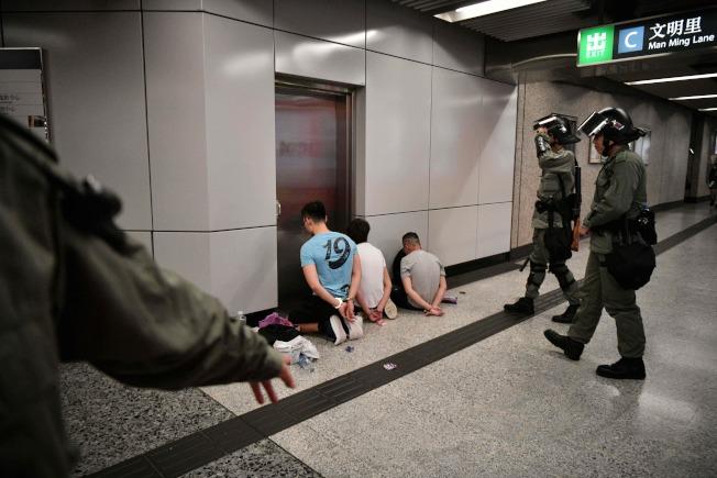 香港831警民衝突,警方在地鐵站內,壓制示威民眾跪地面壁。  (Getty Images)
