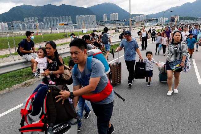 香港警察抵達機場航廈外,並驅散反送中示威者,圖為旅客手拿行李倉皇離開。(路透)
