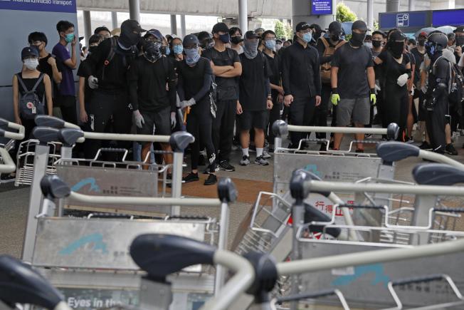 反送中示威者1在香港機場外集合示威,用行李車設下路障。(美聯社)